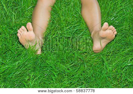 Female  legs are in a green grass