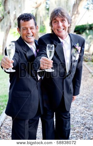Two handsome grooms making a champagne toast at their wedding.
