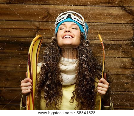 Smiling woman with skies standing against wooden house wall under snow