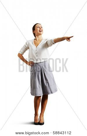 joyous woman pointing at something and laughing. isolated on white background