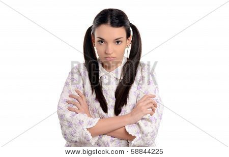 Grumpy in the morning. Beautiful young woman in pajamas upset standing with her hands crossed.