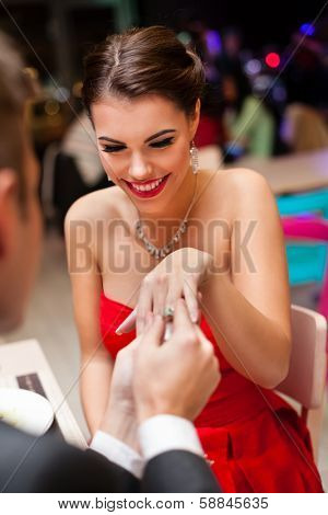 young man proposing with an engagement ring to his love in a restaurant
