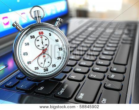 Stopwatch on laptop keyboard. Deadline concept.
