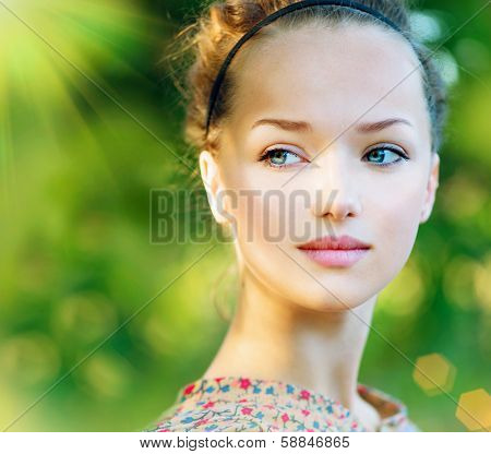Beauty Teenage Model Spring Girl over Nature Green Background. Beauty Girl outdoors. Clean skin. Blue eyes. Beautiful face