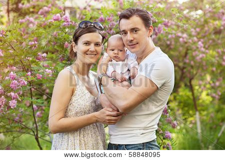 Young couple with newborn son in spring
