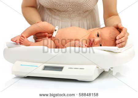 Mother and her newborn baby on a weight scale