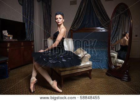 Ballerina in black tutu sitting in front of mirror