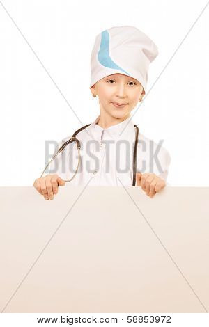 Pretty ten years girl dressed like a doctor holds white board and smiling at camera. Isolated over white.