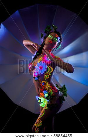 Excited naked woman posing with colorful UV makeup