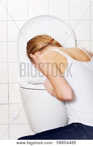 Young caucasian woman is vomiting in the bathroom. Bulimia, sick concept.