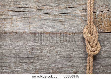 Ship rope knot on old wooden texture background