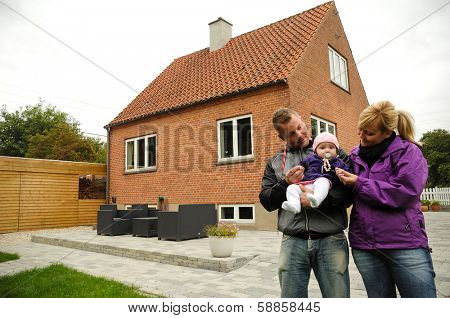 Happy family is standing in front of a house.