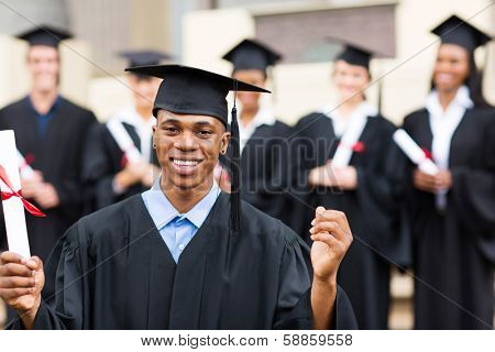 happy african american male college graduate at ceremony