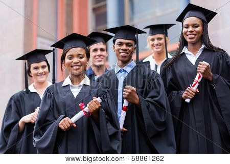 young graduates standing in front of university building on graduation day