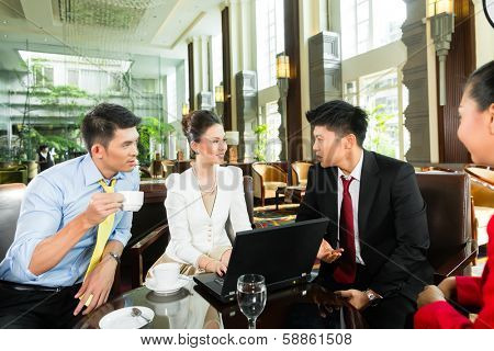 Four Asian Chinese office people or businessmen and businesswomen having a business meeting in a hotel lobby discussing documents on a tablet computer while drinking coffee