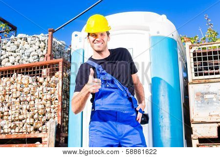 builder using mobile restroom or chemical toilet on construction or building site