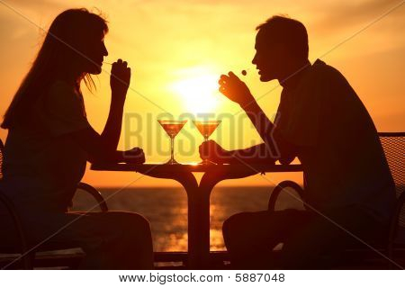 Female And Man's Silhouettes On Sunset Sit At Table