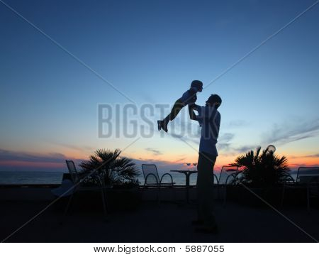 Silhouette Of Man With Child In Hands On Sunset