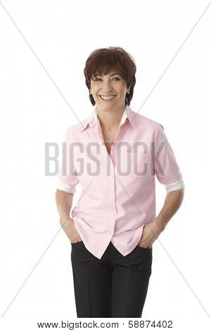 Portrait of mature woman standing hands in pockets, smiling happy.