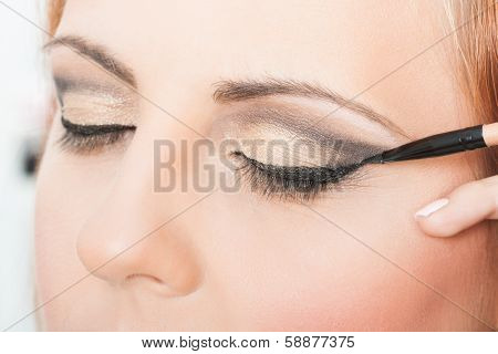 Applying eyeliner
