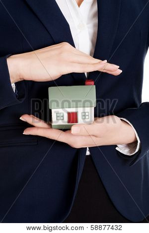 Close up on house modal in business woman's hands on belly.