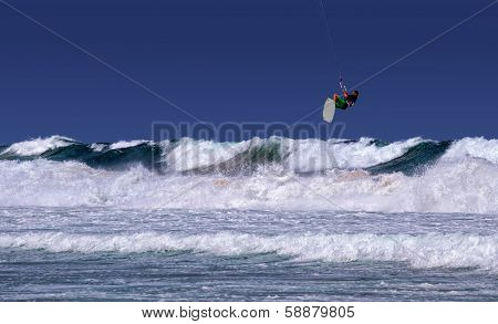 Kite surfer flying off a big wave in rough surf