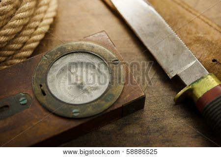 Old knife, compass, and rope on a old wooden desk, Exploration, survival, and hunting concept image.