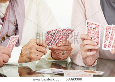 Many hands of senior adults playing cards together