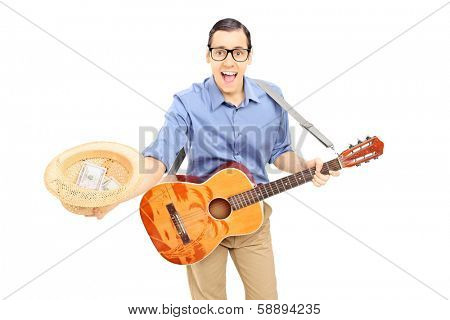 Young male street performer with guitar collecting money in his hat, isolated on white background