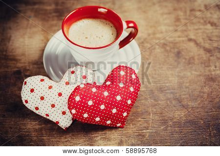 Cup of coffee and heart on wooden background.