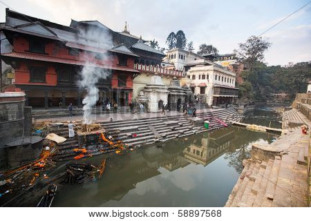 KATHMANDU, NEPAL - DEC 20: During the cremation ceremony along the holy Bagmati River in Bhasmeshvar Ghat at Pashupatinath temple, Dec 20, 2013 in Kathmandu, Nepal.
