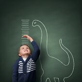 stock photo of dinosaur  - Young boy measuring his growth in height against a blackboard with chalk dinosaur scale - JPG