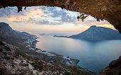 foto of cave woman  - Female rock climber against picturesque view of Telendos Island at sunset - JPG