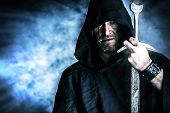 pic of cloak  - Portrait of a courageous warrior wanderer in a black cloak and sword in hand - JPG