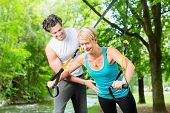 stock photo of suspension  - Fitness woman exercising with suspension trainer and personal sport trainer in City Park under summer trees - JPG