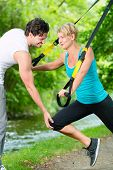 picture of suspension  - Fitness woman exercising with suspension trainer and personal sport trainer in City Park under summer trees - JPG