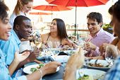 stock photo of chinese restaurant  - Group Of Friends Enjoying Meal At Outdoor Restaurant - JPG