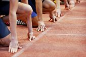 stock photo of race track  - Athletes at the sprint start line in track and field