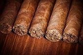cigars on wooden background, closeup view