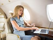 Confident businesswoman with wineglass using laptop in private jet