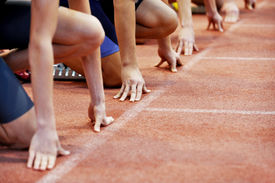 stock photo of track field  - Athletes at the sprint start line in track and field  - JPG