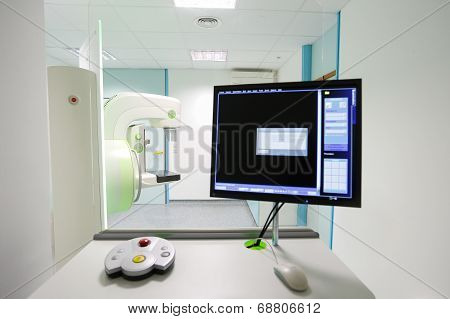 Mammography breast screening device in hospital laboratory with computer display in foreground.