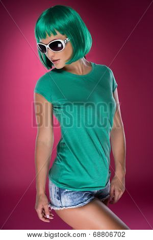 Cute slender young woman with psychedelic green hair in a matching green top, trendy sunglasses and skimpy denim shorts looking down to the side
