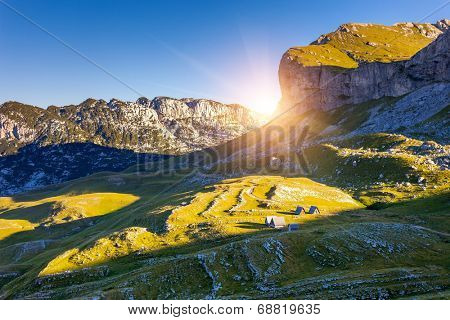 Mountains glow by morning sunlight with shacks in the national park Durmitor in Montenegro, Balkans. Europe. Beauty world.