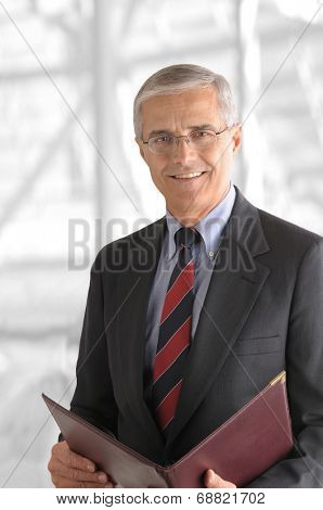 A mature businessman with a leather folder in a modern office building. The background is out of focus and high key.