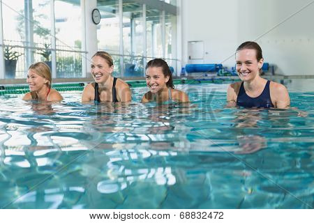 Female fitness class doing aqua aerobics in swimming pool at the leisure centre