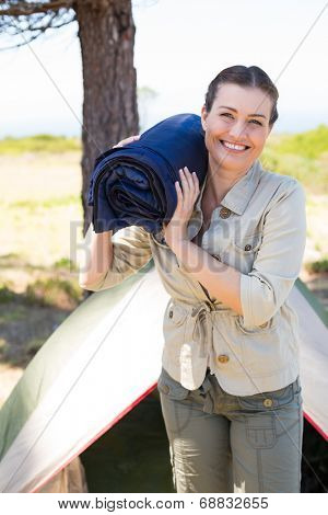 Outdoorsy woman smiling at camera outside her tent on a sunny day