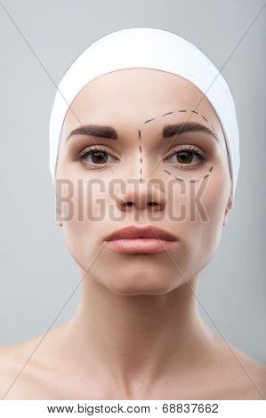 Beautiful young woman with perforation lines on her face before