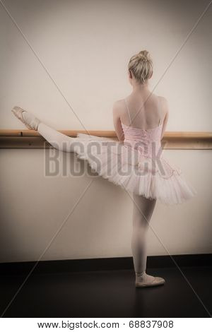 Beautiful ballerina warming up with the barre in the dance studio