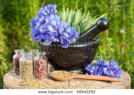 Black Mortar With Blue Cornflowers, Sage, Wooden Spoon And Glass Bottle